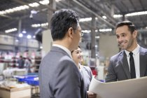 Business people discussing blueprints at industrial factory — Stock Photo