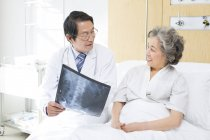 Chinese doctor showing X-ray image to patient — Stock Photo