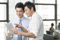 Chinese business people using digital tablet in office — Stock Photo