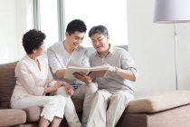 Chinese senior couple with adult son looking at photo album — Stock Photo