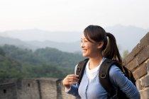 Mujer china con mochila mirando a la vista en la Gran Muralla - foto de stock