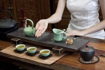 Woman in traditional cheongsam performing chinese tea ceremony — Stock Photo