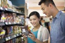 Couple chinois choisissant des marchandises dans un supermarché — Photo de stock