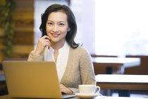 Китайская женщина, сидящая с ноутбуком и чашечкой кофе в кафе — стоковое фото