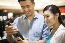 Chinese couple buying wine in supermarket — Stock Photo