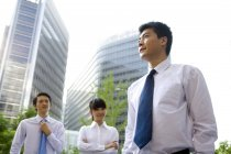Chinese office workers standing in front of skyscrapers — Stock Photo
