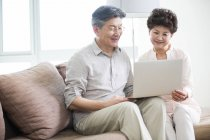 Senior Chinese couple using laptop on couch — Stock Photo