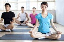 Китайська жінка в клас йоги в турецьки позиції — стокове фото