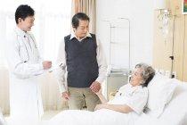 Китайский врач с пожилой парой в больнице — стоковое фото