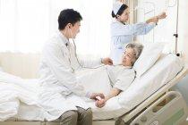 Chinesischen Arzt mit Stethoskop auf Patienten im Krankenhaus — Stockfoto