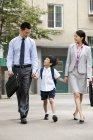 Colegial chinos caminando con sus padres en la calle - foto de stock