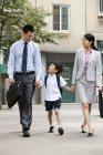 Китайский школьник, прогулки с родителями на улице — стоковое фото