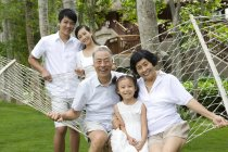 Chinese family with girl resting in hammock — Stock Photo