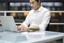 Hombre de negocios chino trabajando con portátil en la oficina - foto de stock