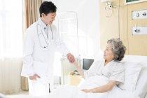 Médecin chinois tenant la main avec le patient à l'hôpital — Photo de stock
