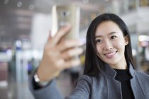 Chinese businesswoman taking selfie with smartphone in airport — Stock Photo