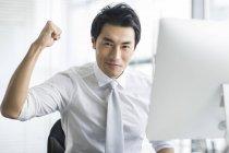 Chinesischer Unternehmer jubeln am Schreibtisch im Büro — Stockfoto