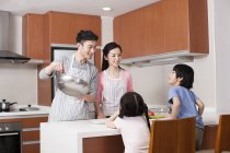 Chinese parents cooking in kitchen with children — Stock Photo