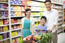 Chinese boy with parents posing while shopping in supermarket — Stock Photo