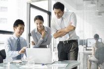 Uomini d'affari cinesi che utilizzano laptop in ufficio — Foto stock