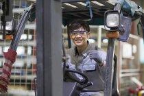 Carrello elevatore guida operaio cinese in fabbrica industriale — Foto stock