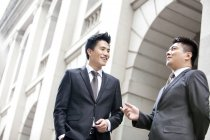 Chinese businessmen talking in front of building — Stock Photo