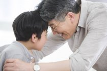 Nonno cinese e nipote premendo fronti — Foto stock
