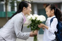 Chinese schoolgirl offering mother bunch of flowers — Stock Photo