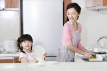 Chinese mother and daughter washing dishes in kitchen — Stock Photo
