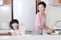 Mãe chinesa e filha lavando pratos na cozinha — Fotografia de Stock