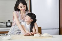 Chinese mother and daughter rolling dough in kitchen together — Stock Photo