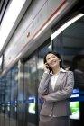 Femme d'affaires chinois, parler au téléphone à la station de métro — Photo de stock