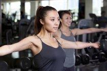 Китайские женщины, поднятие тяжестей в тренажерном зале — стоковое фото