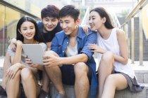 Китайський друзів за допомогою цифровий планшет і, дивлячись — стокове фото
