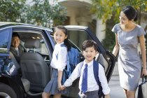 Chinese mother opening car door for children — Stock Photo
