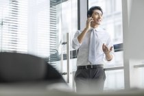 Chinese businessman talking on phone in office — Stock Photo