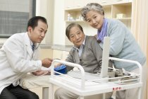Chinese doctor testing senior man blood pressure — Stock Photo