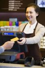 Customer paying by credit card in coffee shop — Stock Photo