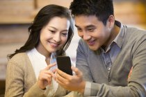Chinese couple using smartphone together in cafe — Stock Photo