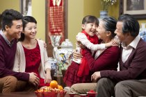Girl embracing grandmother during Chinese New Year with family — Stock Photo