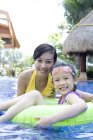 Chinese mother and daughter having fun and looking in camera in pool — Stock Photo