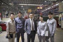 Mature homme d'affaires chinois et l'équipe d'ingénieurs se présentant à l'usine — Photo de stock