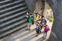 Gruppo di backpackers cinesi che salutano sulla Grande Muraglia — Foto stock
