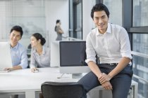 Portrait of Chinese businessman in office with colleagues in background — Stock Photo