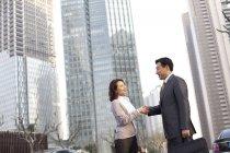 Китайские бизнесмены пожимают руки в финансовом районе — стоковое фото