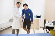 Médico chino ayudar a paciente con muletas - foto de stock