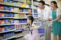 Chinese parents with daughter in cart shopping in supermarket — Stock Photo