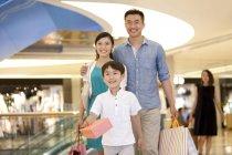 Família chinesa com o filho às compras em loja de departamento — Fotografia de Stock