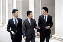 Chinese business team walking and talking on street — Stock Photo