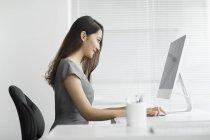 Вид сбоку на предпринимательницу, использующую компьютер в офисе — стоковое фото